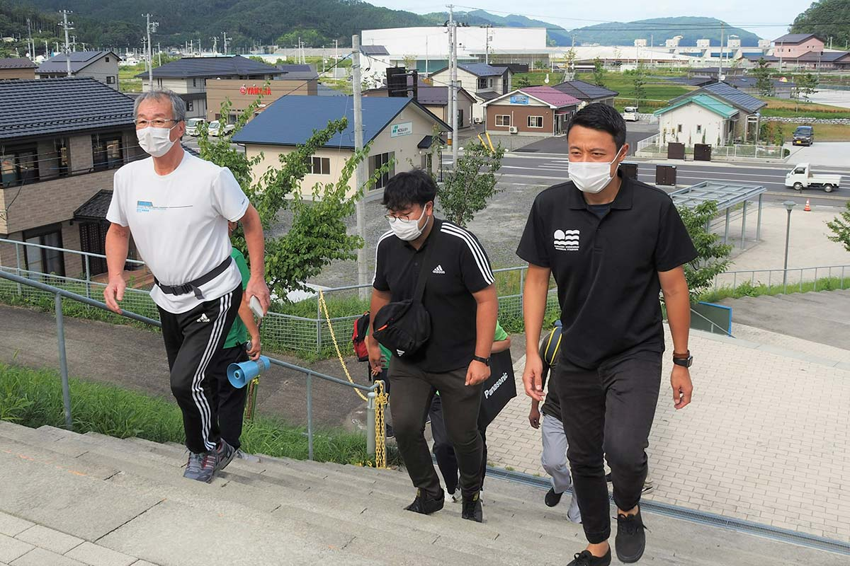 避難先の鵜住居小に続く階段を駆け上がる未来館の職員=3日