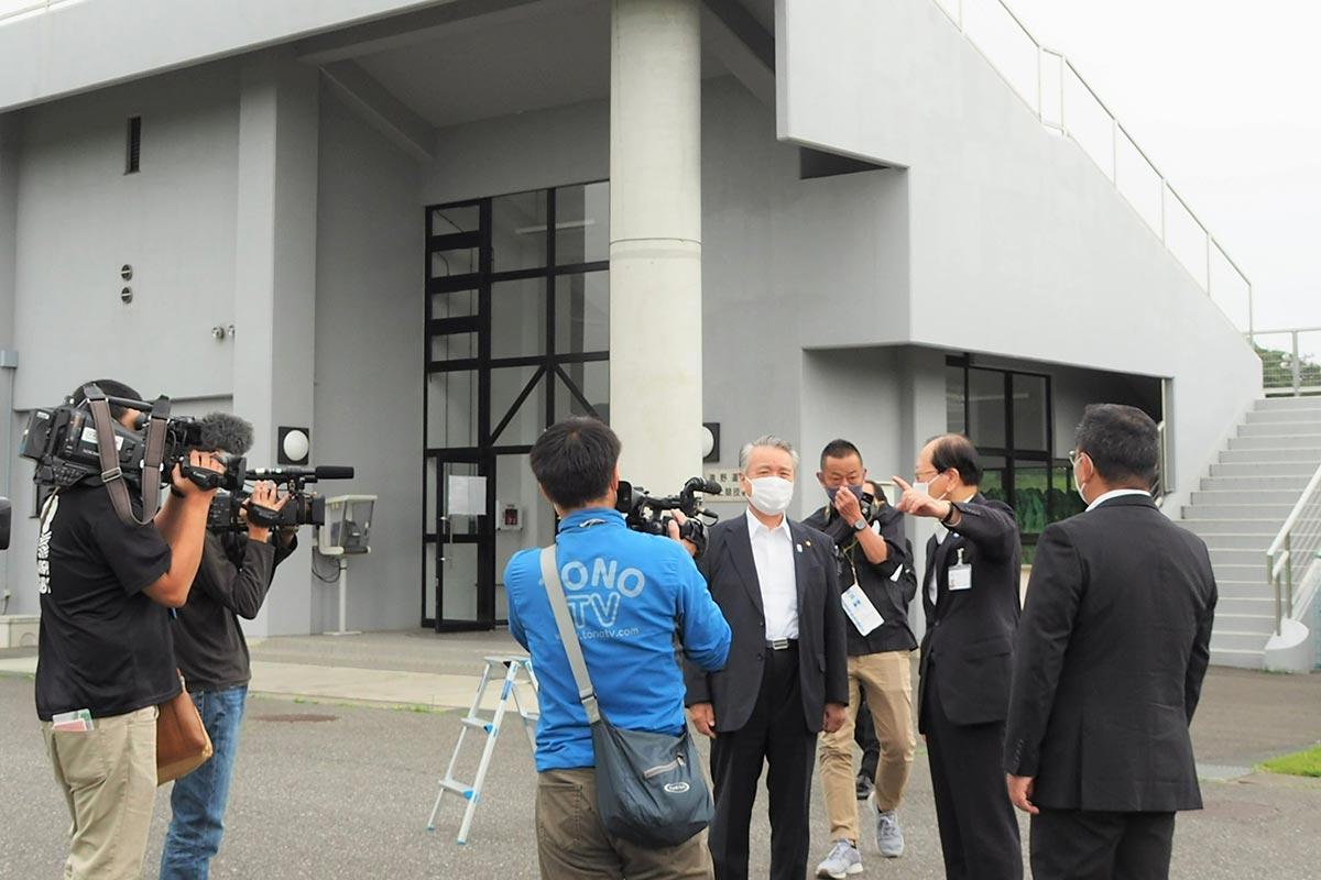現場を視察する両市の関係者ら。背後に建つ陸上競技場管理棟内のトイレも開放される