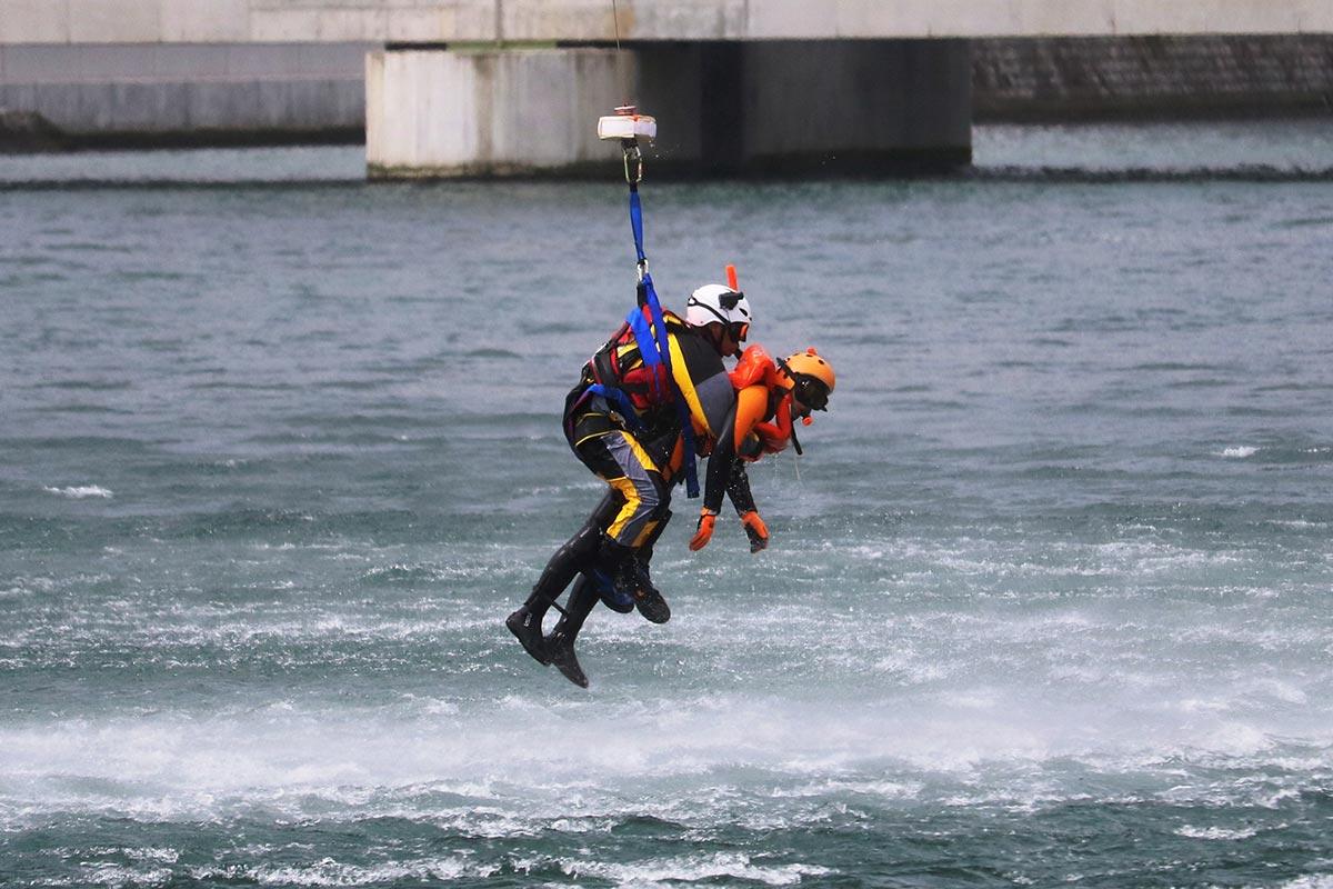 隊員が意識のない要救助者を抱えたまま、ヘリが岸壁上まで移動。救急隊員に引き継いだ