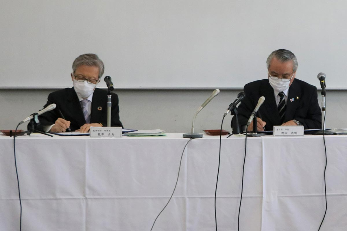 協定書に署名する野田市長(右)と瀧澤理事長=釜石市提供