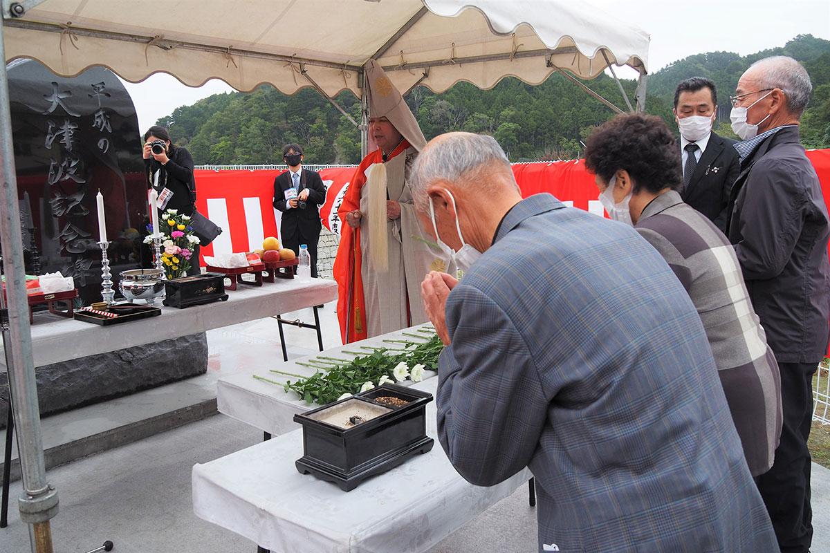 津波記念碑の落成開眼式で犠牲者を悼み、手を合わせる箱崎白浜地区住民ら