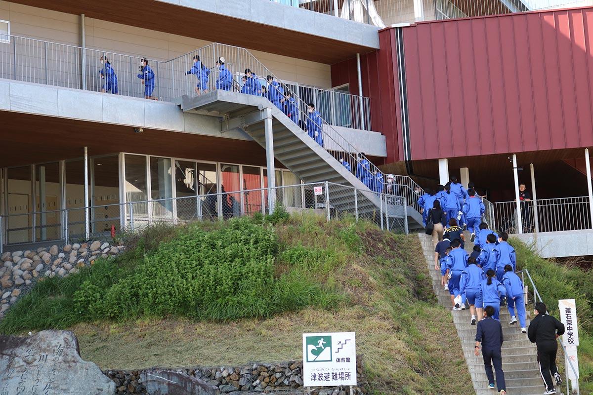 校庭から階段を駆け上がり、より高い広場への避難を始める中学生