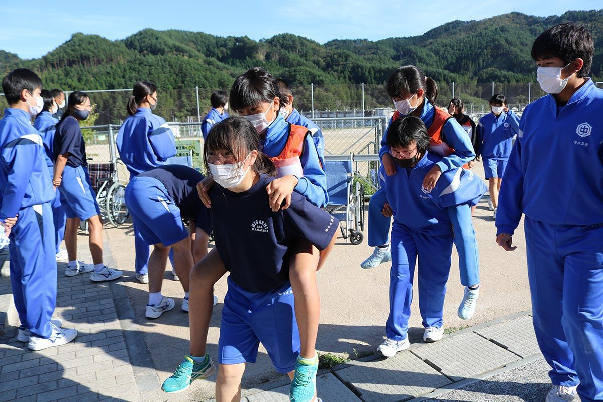 けが人役の小学生を背負い、避難所の体育館に向かう中学生=鵜小・東中合同防災訓練