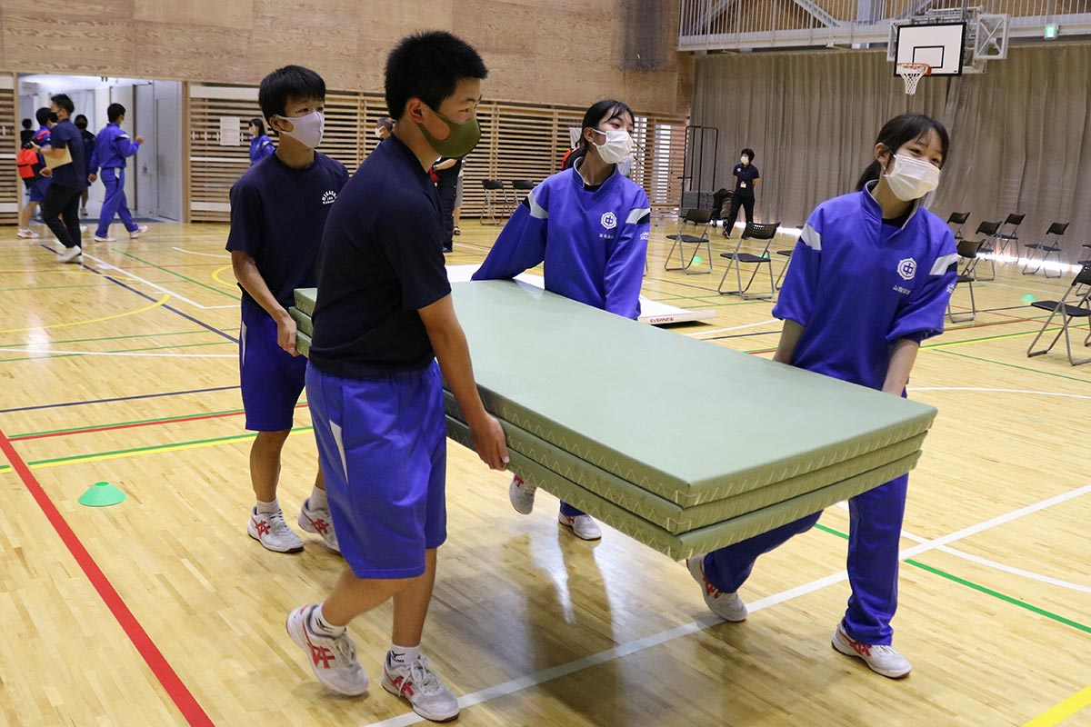 避難者が休めるよう、畳を運び入れる中学生