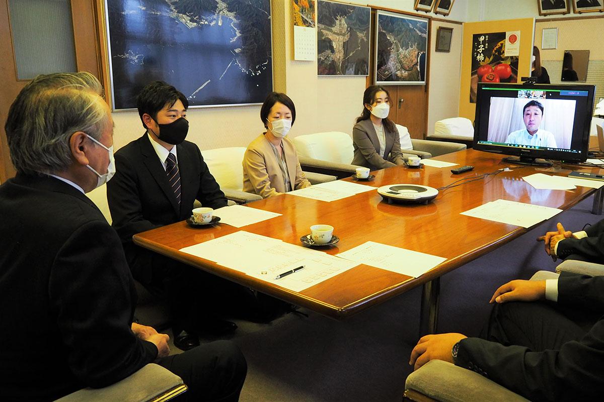 市関係者と懇談する山口さん(左から2人目)と及川さん(画面内)