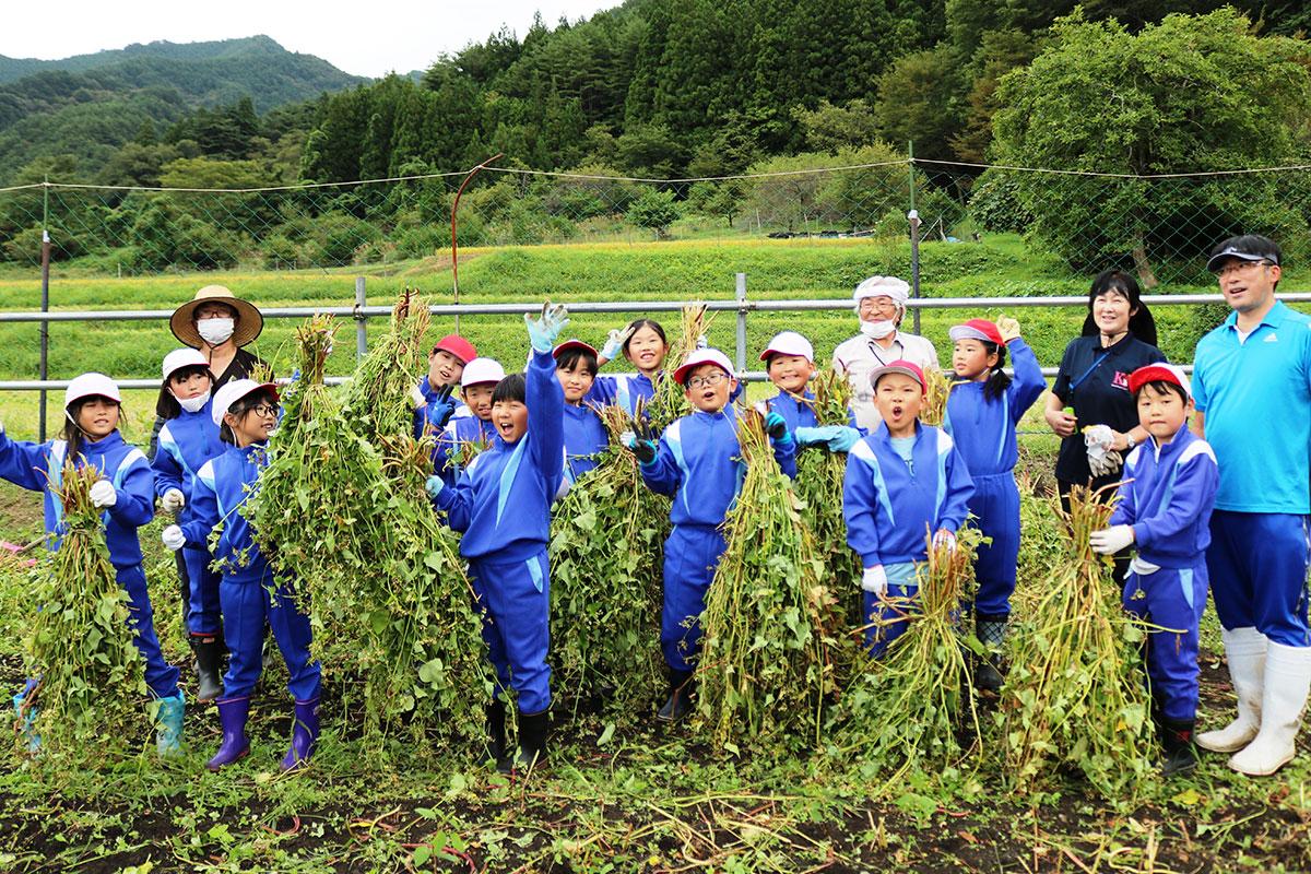 ソバの収穫を喜ぶ栗林小の3・4年生と教員ら